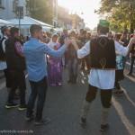 Menschen in Tracht tanzen einen kurdischen Tanz